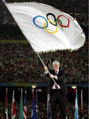 Boris Johnson waves the Olympic flag at the Beijing Olympics Closing Ceremony