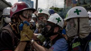 Volunteers - in white helmets with a green cross - have been treating the injured