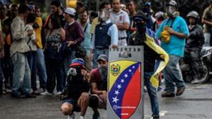 متظاهر يحمل لافتة أمام حشد من المتظاهرين