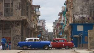 Two classic American cars cross paths in Old Havana.
