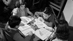 Niños turco-estadounidenses en la mesa con libros de trabajo.