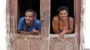 A man and a woman framed by a door frame in Trinidad, Cuba