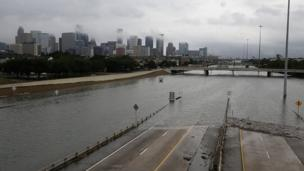 A whole road is pictured submerged with Houston skyline in the distance
