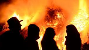 Silhouettes against a bonfire