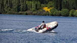 Hombre en un bote pescando salmón en el Lago Moreno en Argentina