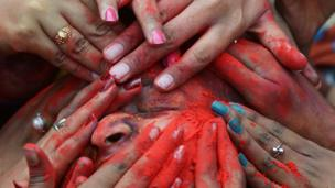 Hands covering face in coloured powder