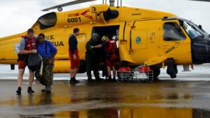 Evacuees leave a US Coast Guard helicopter after being rescued from flooding due to Hurricane Harvey in Houston
