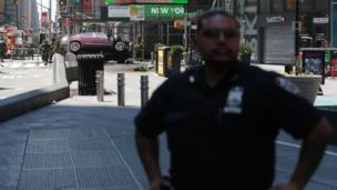 A New York police officer stands guard at the scene of a car accident