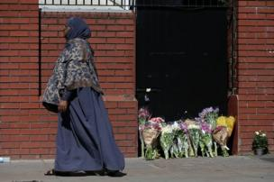 A woman walks past floral tributes outside Finsbury Park Mosque
