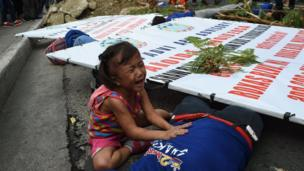A young girl cries as her mother acts as an injured victim during an earthquake drill as part of the metro-wide quake drill in Manila on June 22, 2016.
