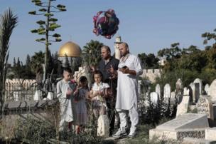 ঈদের দিন জেরুজালেমের আল আকসা মসজিদের কাছে একটি কবরস্তান জিয়ারত করছেন ফিলিস্তিনীরা