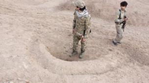جنديان يقفان على حفرة