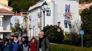 Students and their teacher walk past a street art mural on the facade of a house in Fanzara near Castellon de la Plana
