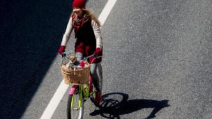 Woman riding bike with dog in basket.