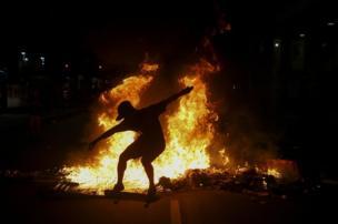 """شاب يمارس حركات تزلج أمام نيران أشعلها محتجون، عقب تظاهرهم ضد إصلاحات مقترحة على الحكومة الاتحادية في """"ريو دي جانيرو"""" في البرازيل"""