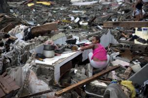 Woman searching through rubble