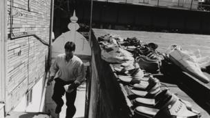 Gawsiah Jame Masjid, subiendo unas escaleras hacia el techo de un edificio, con zapatos tendidos al sol a un lado, en Astoria, Queens, 1997.