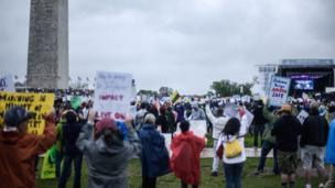 Protesters gather in their hundreds by Washington Monument, next to a stage