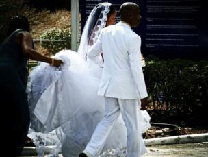 Novio y novia vestidos de blanco rumbo a su boda
