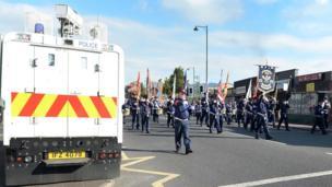 Police van and bandsmen parading past Ardoyne shops in north Belfast, 12 July 2017