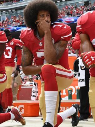 Colin Kaepernick, mariscal de campo de los 49ers, arrodillado durante el himno estadounidense.