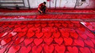 伊拉克库尔德人在埃尔比勒街头为情人节庆祝做准备,他用油漆喷枪为心形图案上红色。