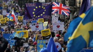 Demonstrators hold placards and wave EU flags as they participate in an anti Brexit, pro-European Union (EU) march in London on March 25, 2017, ahead of the British government's planned triggering of Article 50 next week