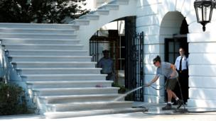 A worker cleans the South Portico porch stairs of the White House with a hose