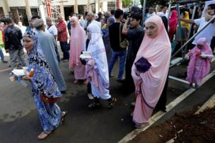 Muslim women walk after praying during Eid al-Fitr at a mosque inside the city hall compound in Marawi City, Philippines, 25 June