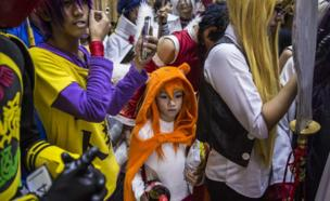 A girl in an orange animal outfit surrounded by taller, older boys in colourful wigs