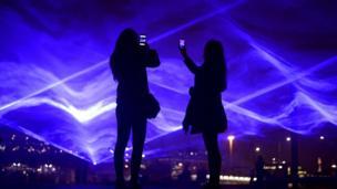 أشخاص يلتقطون صورا لعمل فني، بمنطقة كينغز كروس شمالي لندن