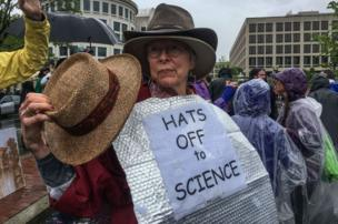Woman with sign reading Hats Off To Science