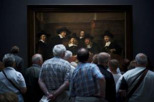 "Second place was Julius Y's photograph, taken in front of Rembrandt's painting Syndics of the Drapers' Guild. By photographing the crowd in front of the painting, he said this, ""gave the illusion that the people in the painting are also curiously watching the visitors""."
