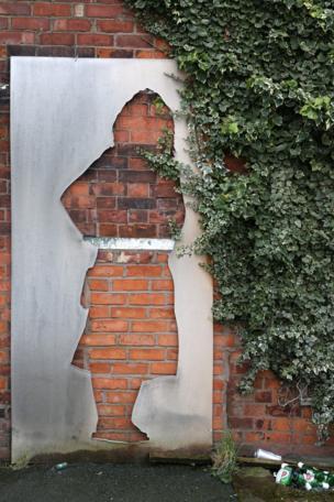 दीवार के सहारे खड़ा कट आउट