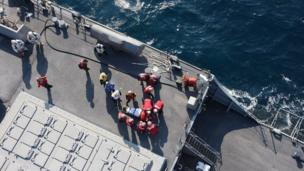 """A handout photo made available by Japan""""s Defense Ministry, showing US military personnel preparing to transfer an injured person on board the USS Fitzgerald"""
