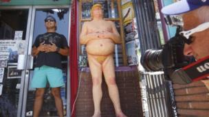 Umugabo umwe yariko arifotoza iruhande y'ico gishusho ca Donald Trump mu gisagara ca Los Angeles