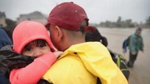 A small child is held in a man's arms after being rescued from the floods.