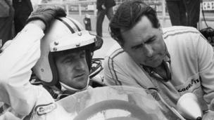 New Zealand racing driver Denny Hulme (1936 - 1992, left) confers with his team mate, Australian racing driver Jack Brabham before a practice run for the British Grand Prix at Silverstone, 13th July 1967.