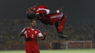 Sudan's Muhannad El Tahir (top) celebrates with a teammate after scoring a goal during their Africa Cup of Nations group I qualification football match at the Al-Merreikh Stadium in Omdurman on 29 March 29