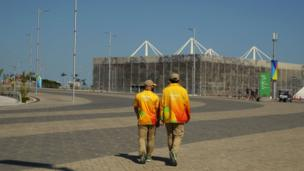 Volunteers walk towards the Olympic Aquatics Stadium in the Olympic Park