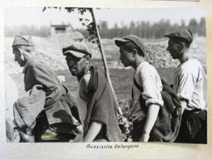 Four men walk in a line, wearing rolled-up shirtsleeves and caps. In the distance, a structure which may be a fortified position can be seen.