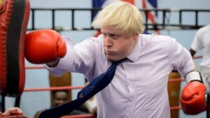 Boris Johnson hitting a punch bag with boxing gloves