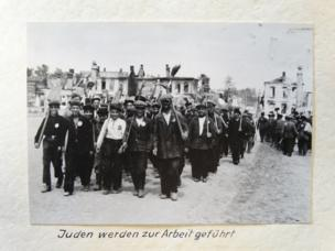 A large crowd of people, wearing the badge marking them as Jewish prisoners, walk in lines, carrying brooms and other work tools.