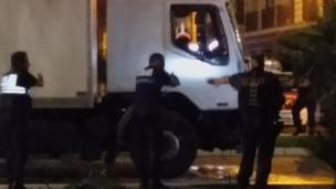 Police shine a light into the lorry's cab as they approach