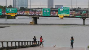 Image shows flood waters on a highway in Houston almost reaching the signs above.