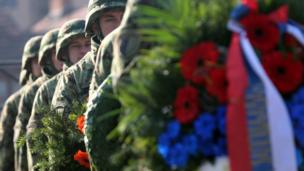 Members of a Serbian military honour guard dey do ceremony for di French military cemetery during Armistice Day