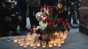 People light candles and lay flowers outside Sennaya Ploshchad metro station after an explosion, in St Petersburg, Russia, 3 April 2017