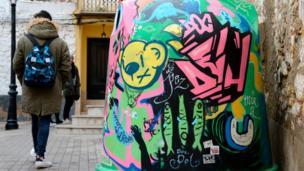 A person walks past a graffiti on a recycling can in Fanzara near Castellon de la Plana
