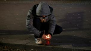Молодой человек зажигает свечку