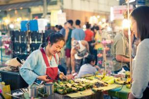 A woman prepares food in a street market